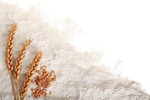 ears of wheat and pile of flour isolated on white background with copy space for your text. Top view. Flat lay