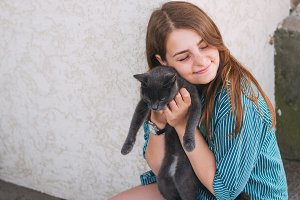 girl hugging a cat