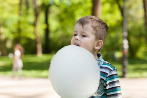 Adorable little boy eating white sweet cotton candy.