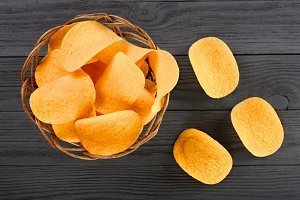 heap of potato chips in wicker basket on black wooden background close-up
