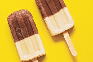 Two chocolate-vanilla ice-cream on a stick on a yellow background. Bright minimalism, the concept of summer.