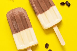 Two-color ice cream on a stick on a bright yellow background with coffee beans. Chocolate-vanilla ice cream. The concept of summer. View from above.