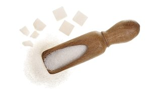 granulated sugar in wooden scoop with cube isolated on white background. Top view. Flat lay