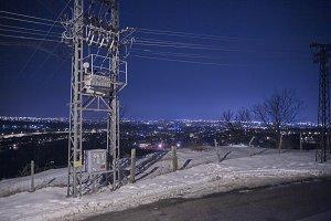 landscape shot, citylights from far away distance, cityscape, power lines, winter snow,