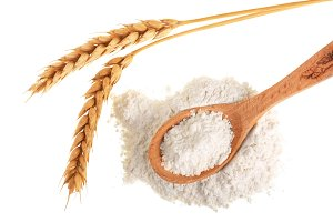 ears of wheat and pile of flour in wooden spoon isolated on white background. Top view. Flat lay