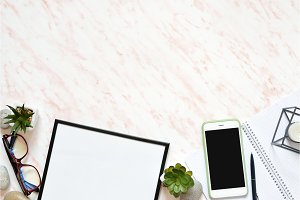 Flat lay office marble desk with phone, frame and notebook copy space background
