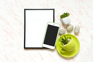 Creative Flat lay marble desk with white empty frame for text, phone, cup, stones and succulents background