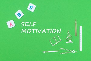 text self motivation, from above wooden minitures school supplies and abc letters on green background