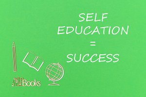 text self education success, school supplies wooden miniatures on green background
