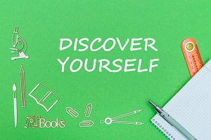 text discover yourself, school supplies wooden miniatures, notebook with ruler, pen on green backboard