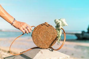 Woman hand with fashionable stylish rattan bag and silk scarf on the ocean background. Tropical island of Bali, Indonesia. Rattan handbag and silk scarf.