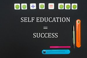 Black art table with stationery supplies with text self education success on blackboard