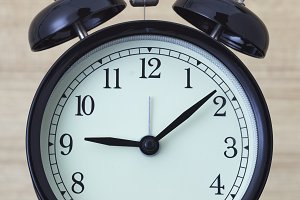 Black retro alarm clock on wood table