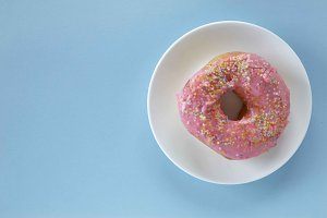 Pink round donut on pastele background