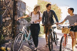 Friends with bikes walking outdoors