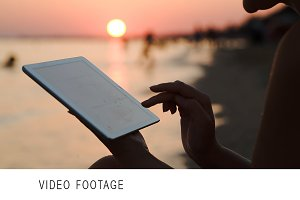 Girl working with tablet PC on beach