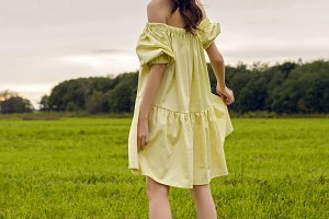 woman in yellow dress stands in a field