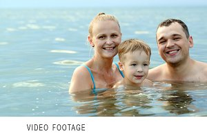 Happy family of three in the sea