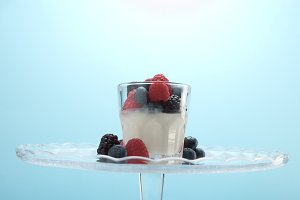 transparent glasses full of yogurt, panna cotta, white vanilla mousse decorated with berries