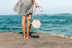 Woman with fashionable stylish white rattan bag and silk scarf outside. Tropical island of Bali, Indonesia. Rattan handbag and silk scarf.