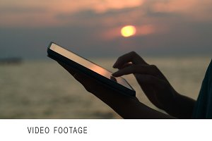 Using touchpad on the beach sunset