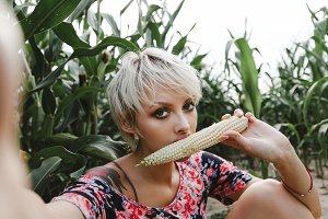 Girl between green leaves in a corn