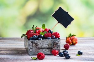 Fresh mix of berries in a metal box on white stone background