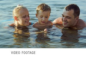 Parents and son in sea during summer