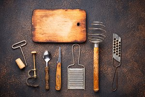 Old vintage kitchen utensils on rusty background
