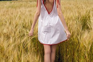 woman in a red light dress stands in a field
