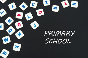 english colored square letters scattered on black background with text primary school