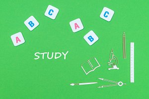 text study, from above wooden minitures school supplies and abc letters on green background
