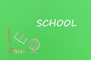 text school, school supplies wooden miniatures on green background