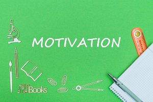 text motivation, school supplies wooden miniatures, notebook with ruler, pen on green backboard