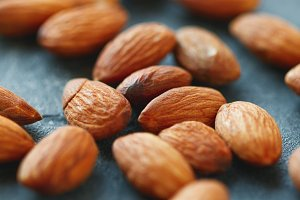 Almond nuts over grey background