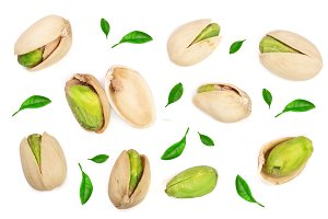 Pistachios decorated with leaves isolated on white background, top view. Flat lay pattern