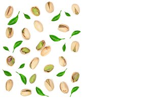 Pistachios decorated with leaves isolated on white background with copy space for your text, top view. Flat lay pattern
