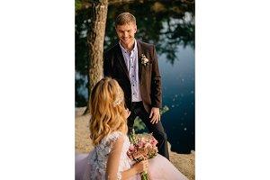 happy newlyweds on the lake shore