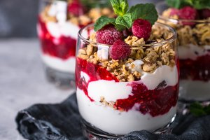 Yogurt parfafait with granola and raspberries in glass.