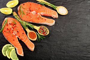 Slice of red fish salmon with lemon, rosemary on black stone background with copy space for your text. Top view