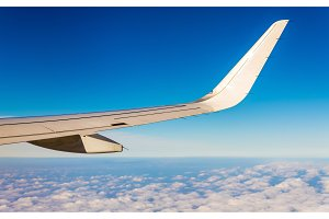 Aircraft wing flying over clouds