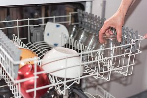 woman's hand loading the dishwasher