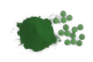 Spirulina algae powder and pills isolated on white background. Top view