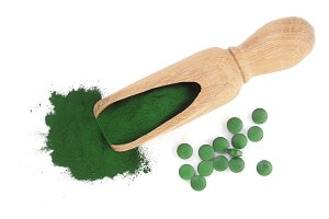 Spirulina algae powder and pills in wooden scoop isolated on white background. Top view
