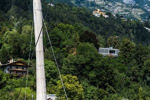 Cable railway bridge against Alps mountains