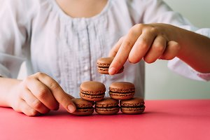 Woman placing macarons on heap on pink table