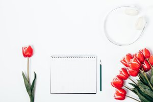 Red tulips, headphones and notebook