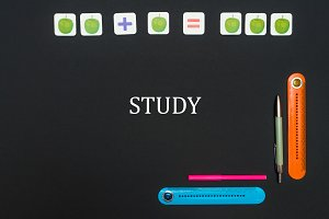 Black art table with stationery supplies with text study on blackboard