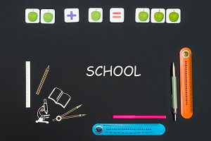 Above stationery supplies and text school on blackboard