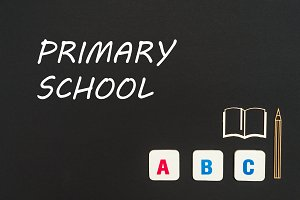 abc letters and chipboard miniature on blackboard with text primary school